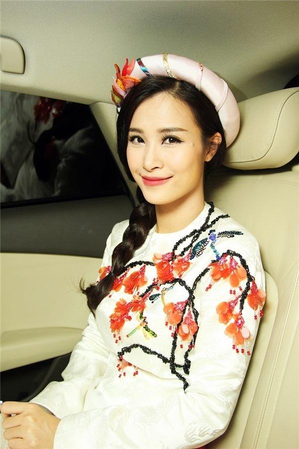 Trên nền trắng, bộ trang phục của Đông Nhi được tạo điểm nhấn bằng họa tiết hoa đào đính kết bằng cườm, đá. Chiếc mấn kết hợp đồng điệu về màu sắc, chi tiết với trang phục.
