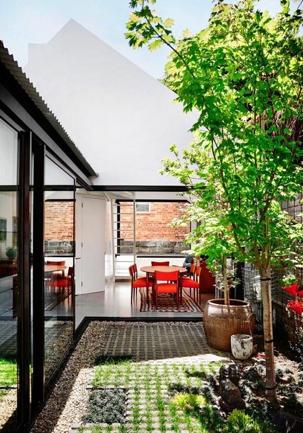 Khoảng không gian chính được kết nối với mảnh sân nhỏ, nơi có cây xanh và ngập tràn nắng gió. Chính bởi vậy, bộ bàn ghế ăn sum họp của gia đình cũng trở nên dễ chịu và thông thoáng hơn.