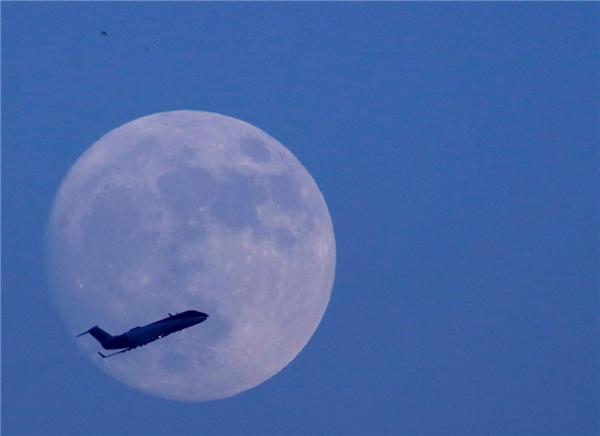 Máy bay bay ngang qua bầu trời Kathmandu ở Nepal, với hậu cảnh mặt trăng. (Ảnh: Reuters)