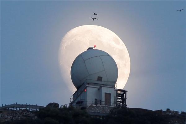 Trăng rằm dần xuất hiện trên nóc một tháp quan sát tại vùng lãnh thổ Gibraltar của Anh. (Ảnh: Reuters)