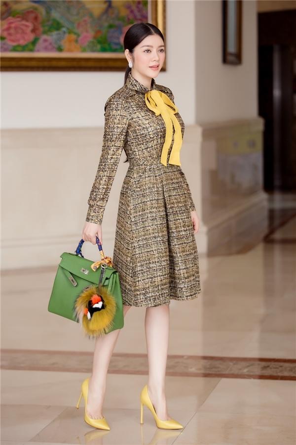 Lý Nhã Kỳ hóa thân thành quý cô châu Âu cổ điển với váy xòe ngang gối màu trầm khi đến tham gia một hội nghị. Nữ diễn viên, doanh nhân khéo léo nhấn nhá cho bộ trang phục bằng nơ thắt, giày cao cùng túi xách với hai tông màu vàng, xanh nổi bật. Các thành phần đều là hàng hiệu và có giá vô cùng đắt đỏ.