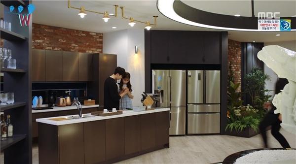 Ấn tượng đầu tiên khi bước vào căn hộ chính là tông màu đen kết hợp ánh đèn vàng mang hơi hướng hoàng gia sang trọng. Khu vực phía dưới sẽ dành cho phòng khách, bếp, kệ chứa rượu… Cầu thang nối giữa hai tầng cũng được thiết kế ấn tượng và đặt ở vị trí thuận tiện do sự di chuyển.