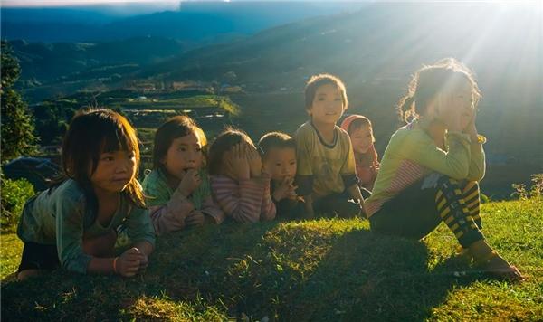 Những đứa trẻnằm dài trên bãi cỏ ven đường.(Ảnh: Phạm Nhất Việt)