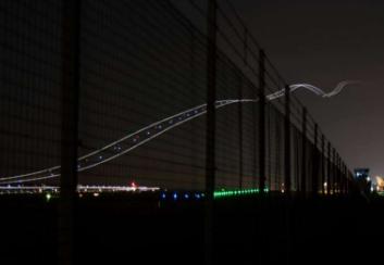 Đường ánh sáng trên bầu trời đêm khi máy bay vừa bay qua.