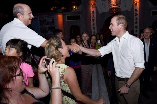 Hoàng tử không ngại bắt tay, trò chuyện và cười tươi cùng các du khách.(Ảnh: Giang Huy)