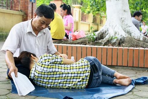 Hình ảnh gây xúc động nhất mùa tuyển sinh Đại học - Cao đẳng 2012: ông Nguyễn Xuân Lữ (48 tuổi) quạt bằng xấp giấy cho con gái ngủ suốt buổi trưa để chuẩn bị vào môn thi thứ hai.(Ảnh: Internet)