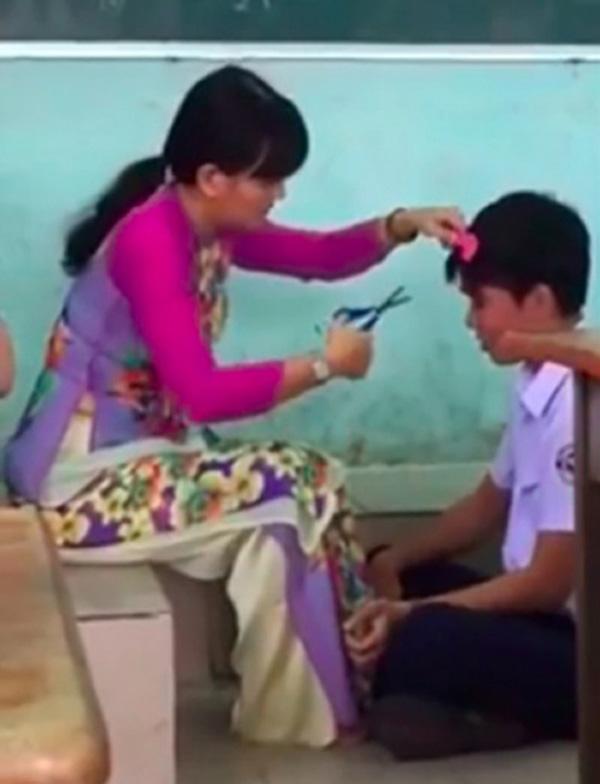Hình ảnh cô giáo cắt tóc cho cậu học trò ngay trong lớp học.(Ảnh: Internet)
