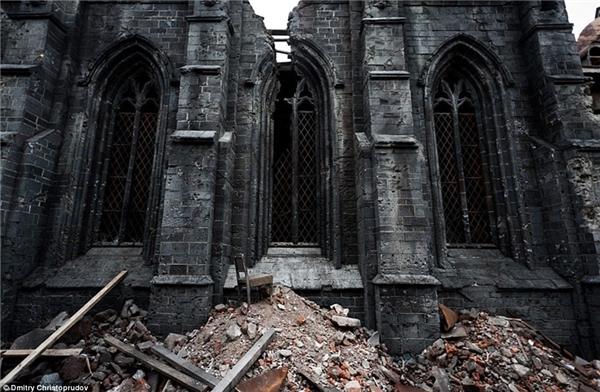 Hình ảnh một đống đổ nát với chiếc ghế và những tấm ván gỗ nằm phía trước một nhà thờ bị tàn phá nặng nề.