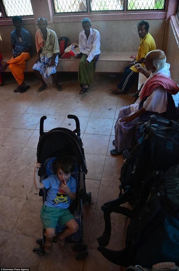 Alfred tại trạm chờ xe buýt ở Sri Lanka, Ấn Độ bên cạnh rất nhiều người tị nạn.