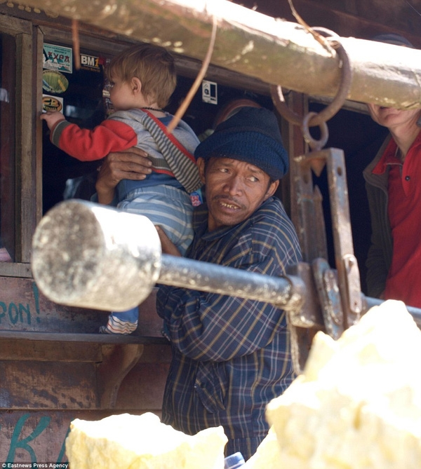 Cậu bé được người bản địa tại Java, Indonesia giúp đỡ.