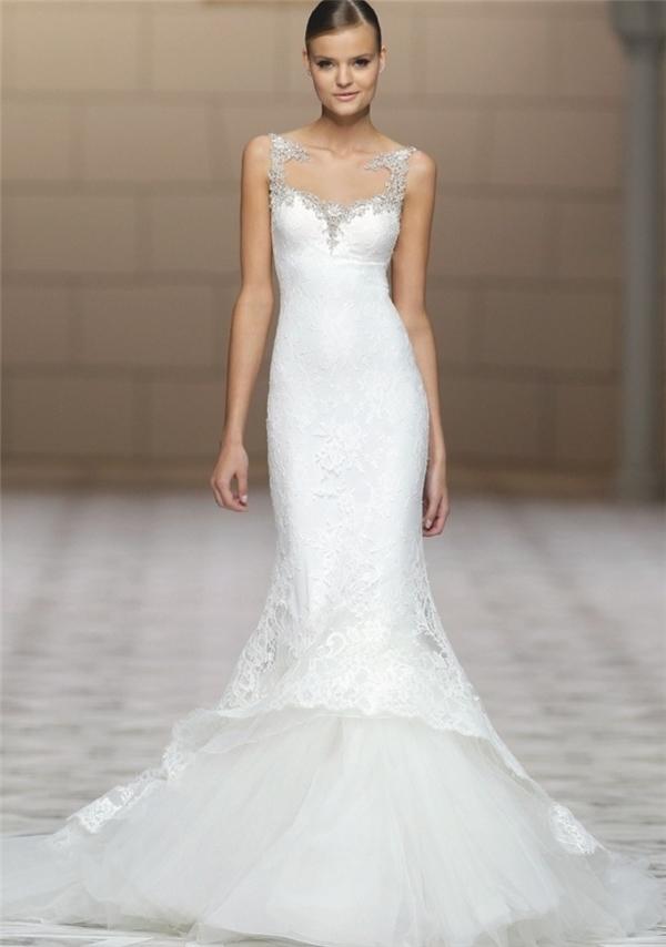 Váy cưới đuôi cá ren chìm ấn tượng với các họa tiết đính đá cầu kỳ, tinh tế ở vai và ngực áo. Phần đuôi váy được may bằng nhiều lớp vải chiffon bồng bềnh