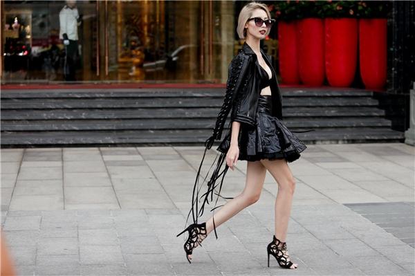 Hằng Nguyễn diện cả cây đen kết hợp giữa bratop, chân váy xòe cùng áo khoác da cá tính. Chi tiết tua rua giúp tổng thể trở nên mềm mại hơn.