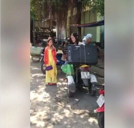 Cô bé đứng hát cùng cha bên chiếc xe ba gác cũ kĩ. (Ảnh: Cắt clip)