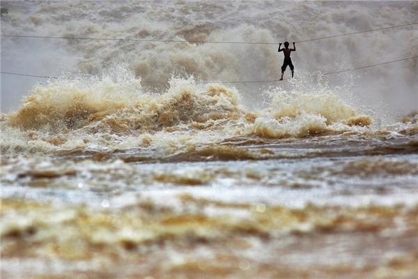 Vào mùa mưa, ông Samnieng - một ngư dân Lào - tự chế một cây cầu từ hai sợi dây chắc để băng qua sông Mekong tại tỉnh Champasak, Lào.