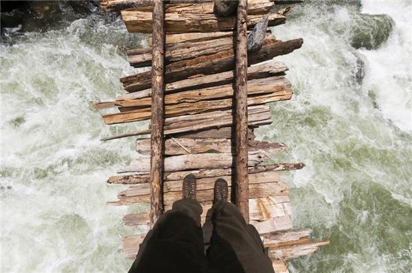 Một phượt thủ băng qua cây cầu gỗ bắc ngang sông Kanka thuộc Naranag, khu vực Hồ Gangabal, Kashmir Himalayas, Ấn Độ.