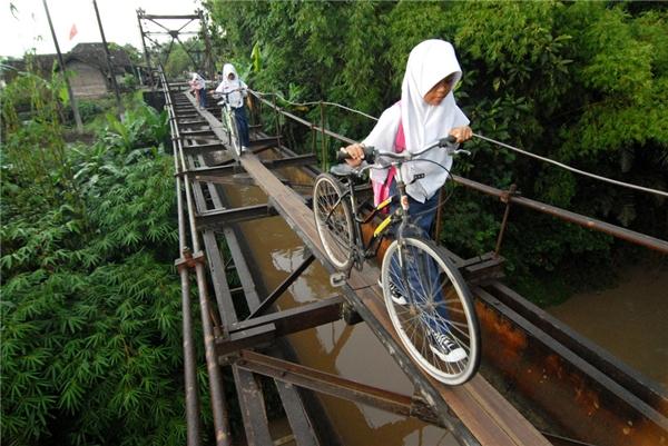 Các học sinh người Indonesia đến trường nhờ cây cầu nối giữa làng Suro và làng Plempungan ở Boyolali, Trung Java, Indonesia.