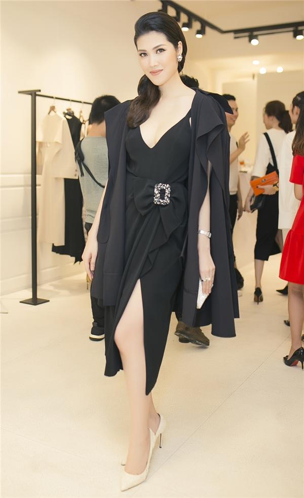Cô chọn cho mình chiếc đầm đen xẻ tà khoét ngực sâu, tôn chuẩn dáng đồng hồ cát và làn da trắng sáng không tì vết, phối cùng áo cách điệu khoác trễ vai hững hờ.