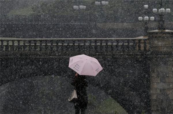 Một du khách đã chụp ảnh trong ngày tuyết rơi đầu mùa.(Ảnh: Reuters).