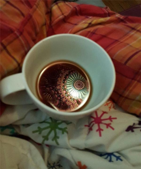 """Trần nhà rực rỡhiện lên thật sống động bêntrên lớp """"gương"""" cà phê."""