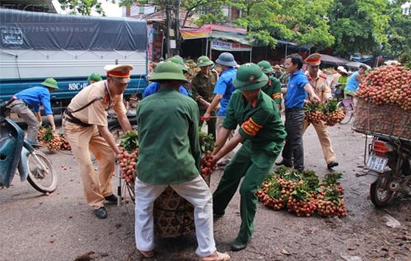 Chiến sĩ CSGT giúp dân dọn vải thiều bị rơi ra đường. (Ảnh: Internet)