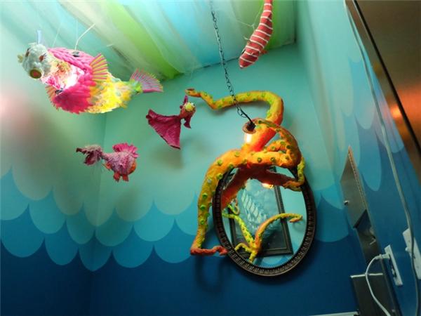 Trên trần có treo những sinh vật biển ngộ nghĩnh làm từ muỗng nhựa, hệ thống đèn sặc sỡ, và một tấm gương lớn bị một con bạch tuột khổng lồ chiếm giữ.