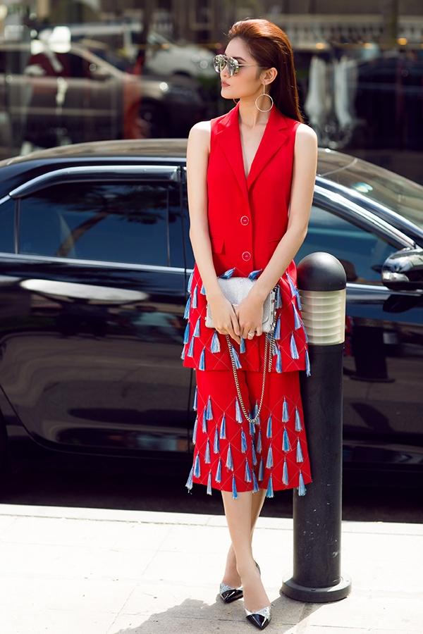 Quần culottes phối áo suit dáng dài không tay quen thuộc trở nên mới lạ hơn nhờ những đường dây mỏng manh đan chéo cùng chi tiết tua rua đính kết theo cấu trúc đối xứng. Hai tông màu xanh đỏ thường ít được kết hợp với nhau nhưng nhà thiết kế Jenny Kim lại liều lĩnh tạo nên tổng thể trông khá thú vị này.