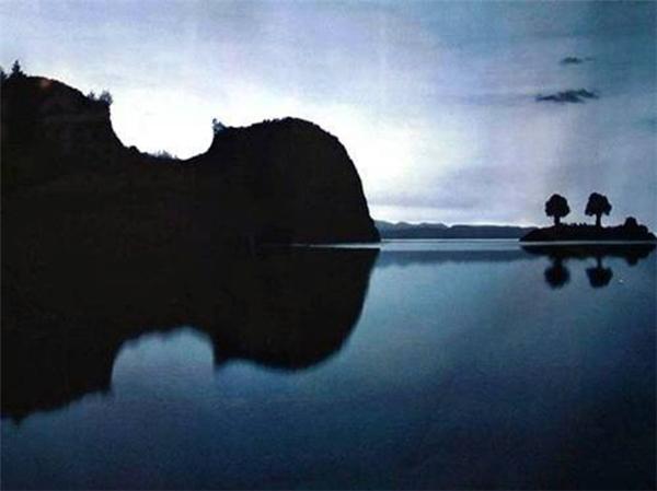 Hình ảnh ngọn núi và một cái gò nhỏ nằm giữa hồ trong khung cảnh chuẩn bị chào đón ánh bình minh trông khágiống cây đàn ukulele khổng lồ trên mặt nước.