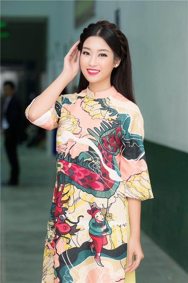 Đi chấm thi nhan sắc, Đỗ Mỹ Linh chọn phong cách dịu dàng, nữ tính với áo dài của nhà thiết kế Thủy Nguyễn, tóc tết tạo thành băng đô ở trước và để xõa ở sau, trang điểm tự nhiên, nhẹ nhàng.