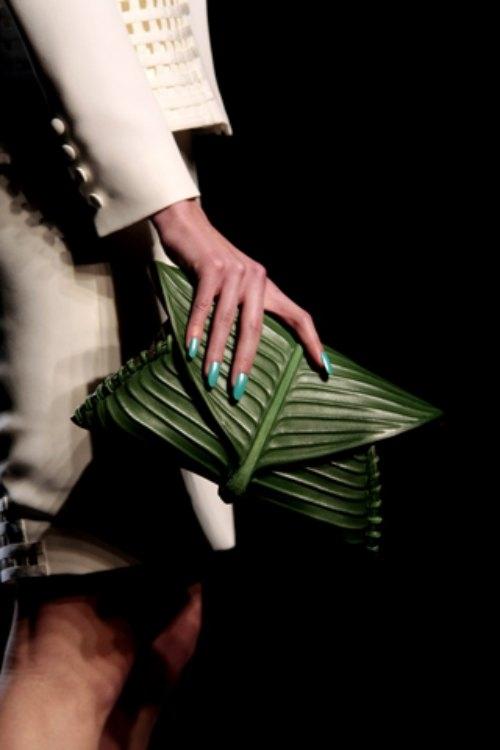 Khi người mẫu Karlie Kloss xuất hiện trên sàn diễn, bên cạnh bộ trang phục thì chiếc ví cầm tay của cô nàng được chú ý mạnh mẽ. Thiết kế trông như một tàu lá chuối non được quấn lại.