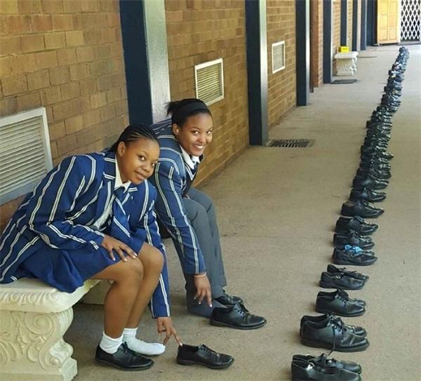 Những học sinh năm cuối đang cởi từng chiếc giày để tặng.