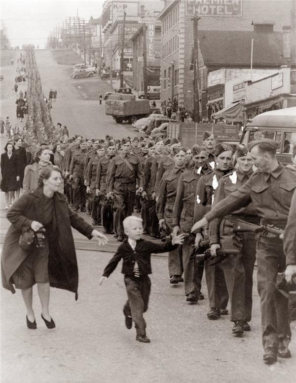 """#2 """"Chờ con với, cha ơi!"""". Bức ảnh trắng đen này được chụp vào ngày 1/10/1940, khi những người lính ở British Columbia đang xếp hàng để bước lên xe lửa thì cậu bé Whitey Bernard, 5 tuổi, chạy khỏi vòng tay mẹ để chạm vào cha mình."""