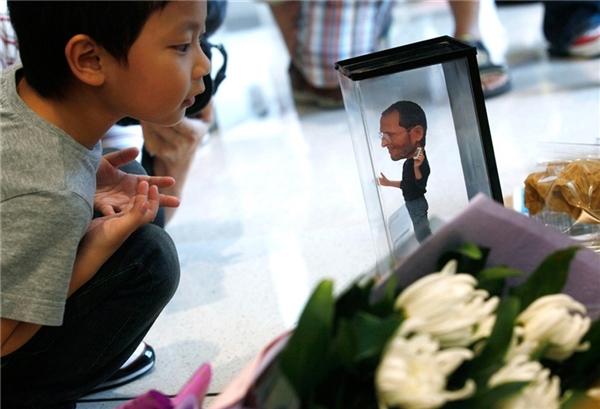 #10Một cậu bé chăm chú nhìn bức tượng nhỏ của người sáng lập kiêmcựu CEO của hãng Apple -Steve Jobs - tại nơi người ta đặt những vòng hoa để tưởng niệm ông ngay trong một cửa hàng Apple ở Hong Kong vào ngày 6/10/2011.