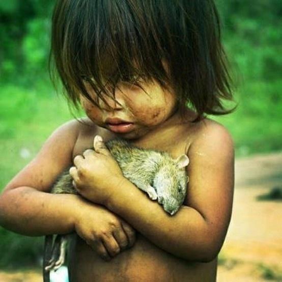 #12Một bé gái người Guarani ôm một con chuột chết.