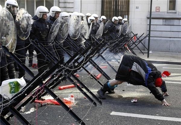 #13Hành động thể hiện sự phản đối gay gắt của một người biểu tình trước dàn cảnh sát chống bạo động trong một cuộc biểu tình công nhân châu Âu và đại diện công đoàn nhằm yêu cầu đảm bảo việc làm tốt hơn ở các nước Liên minh châu Âu, diễn ra tại Brussels vào ngày 24/3.