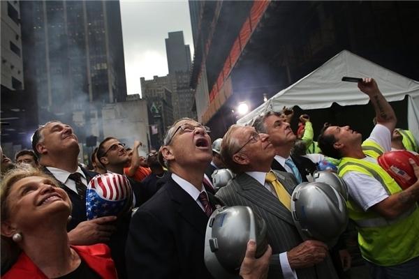 #14 Người dân đang chăm chú theo dõi chiếc dầm thép cuối cùng của Trung tâm Thương mại Thế giới, có chữ ký của các thành viên của phi hành đoàn đã giúp xây dựng tòa tháp, được treo ở độ cao 977 feet.