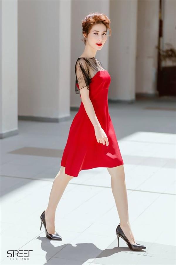 Trong loạt trang phục dạo phố, Diễm My vẫn không quên chọn một chiếc đầm đỏ có phom đơn giản kết hợp chất liệu ren ở cầu vai.
