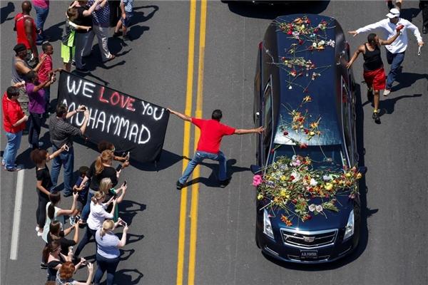 """10/06: Tấm banner ghi dòng chữ """"Chúng tôi yêu ông, Muhammad"""" đã được giăng ra trong lúc những người đi đưa tang chạm vào chiếc xe chở thi hài huyền thoại quyền Anh Muhammad Ali băng qua Louisville, Kentucky."""