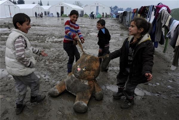 15/03: Các trẻ em tị nạn đang chơi đùa rất vui vẻ với một chú thỏ bông tại một khu trại dựng tạm bợ trên mặt đất bùn lầy nhơ nhớp ở biên giới Hy Lạp - Marcedonia, gần ngôi làng Idomeni, Hy Lạp.