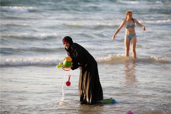21/08: Một phụ nữ Hồi giáo đang mặc Hijab và một phụ nữ Israel đang đứng gần đó trên bãi biển Tel Aviv, Israel.