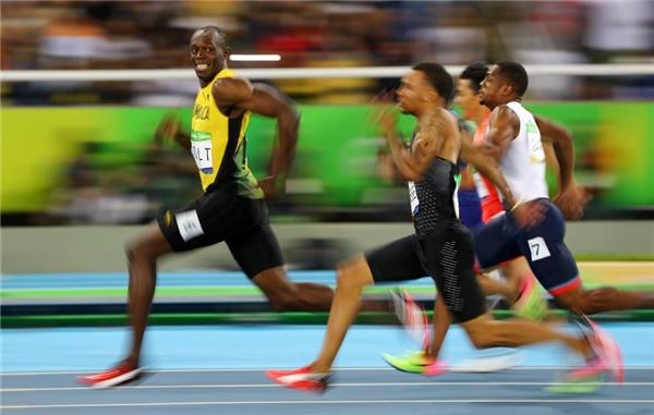 14/08: Usain Bolt người Jamaica quay lại nhìn Andre De Grasse người Canada trong vòng bán kết điền kinh 100m nam ở Olympics Rio.