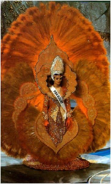 """Tuy nhiên, trang phục truyền thống của Khả Trang vẫn chưa thể so sánh được với thiết kế mà Hoa hậu Parguay Pamela Zarza mang đến Miss Universe 1992 diễn ra tại Thái Lan. Do độ cồng kềnh cùng khối lượng """"khủng"""" của bộ trang phục mà Hoa hậu Paraguay đã được đặccách đứng im một chỗ và có người lắp ráp trang phục cho cô."""