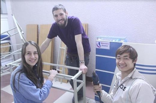 Hòa cùng các tình nguyện viên làm bàn cho lớp học mới.
