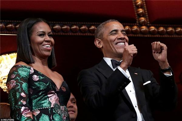 Bà Obama mặc một bộ đầm đen sang trọng điểm lá xanh và hoa màu hồng lấp lánh.