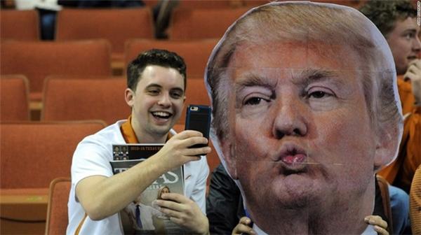 Một cổ động viên selfie cùng bức hình tân tổng thống Donald Trump trước khi trận bóng rổ diễn ra ở nhà thi đấu trường đại học Texas, Mỹ ngày 12/1.