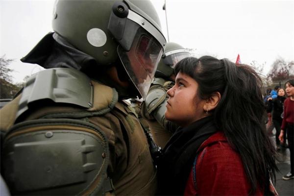 Một ánh mắt đầy thách thức của người biểu tình khi nhìnviên cảnh sát chống bạo động đã gây chấn động cộng đồng mạng. Bức hình được chụp trong cuộc biểu tình kỉ niệmcuộc đảo chính 1973 tại Santiago, Chile vào ngày 11/9/2016.