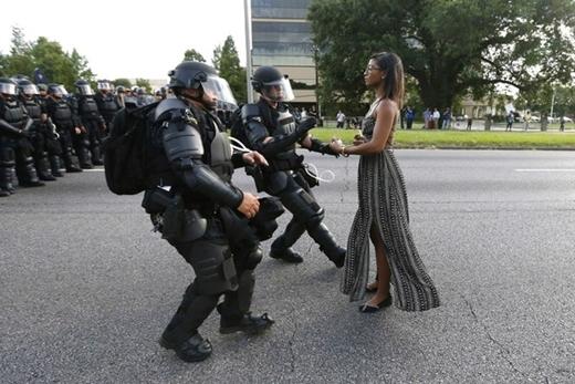 9. Vào tháng 7, một cô gái biểu tình bị chặn lại trước Sở Cảnh sát thành phố Baton Rouge (Louisiana, Mỹ) trong một vụ đụng độ sau khi cảnh sát bắn chết Alton Sterling - một người dân da màu.