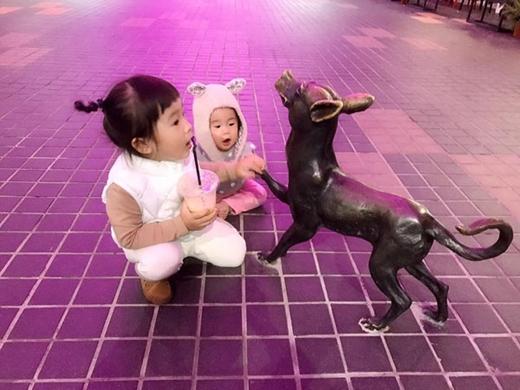 Bé Meng Meng chơi đùa cùng em trai cạnhbên tượng chú chó.