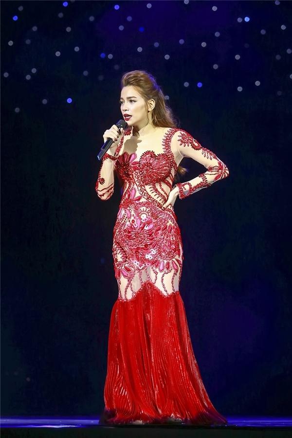 Bộ váy màu đỏ cũng không hề kém cạnh với hàng nghìn viên đá được đính kết tạo họa tiết cho phần chất liệu xuyên thấu.