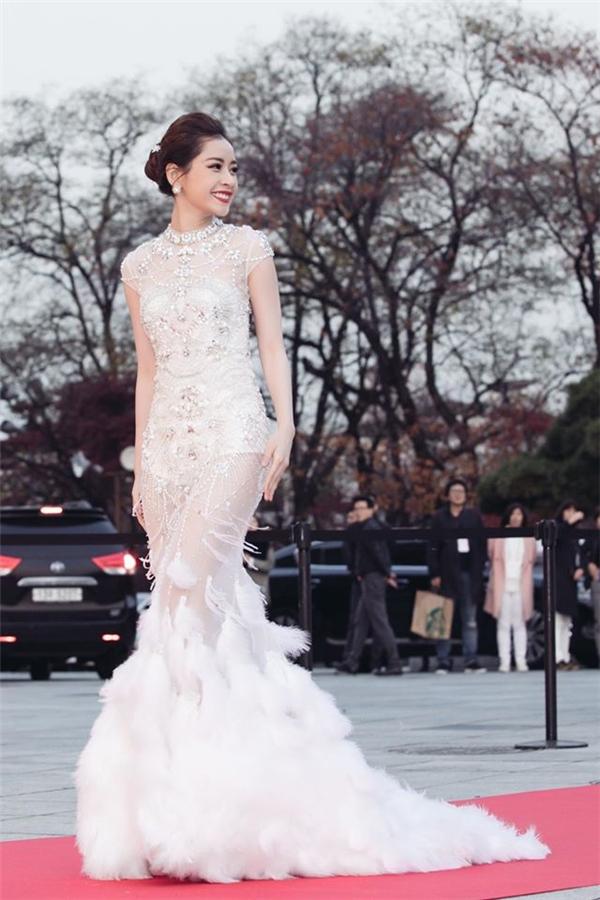 Trên thảm đỏ tại Hàn Quốc vào cuối tháng 11 vừa qua, nữ diễn viên trẻ cũng khiến công chúng mãn nhãn với bộ váy đuôi cá xuyên thấu kết hợp chi tiết lông vũ ở phần đuôi, đá cườm tạo họa tiết ở thân váy. Thiết kế như tái hiện hình ảnh nàng thiên nga trắng duyên dáng, tinh khôi nhưng không kém phần quyến rũ.