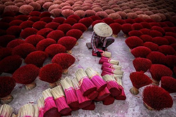 """Bức ảnh """"Cánh đồng hương"""" được bình chọn là ảnh đẹp nhất ngày 3/12 trên mục Your Shot. Những người thợ làm hương truyền thống ngồi giữa hàng chục bó hương đầy màu sắc được xếp lại cẩn thận. Độc giả nhận xét bức ảnh có màu sắc và bố cục đẹp, đồng thời kể được câu chuyện ý nghĩa về nghề làm hương truyền thống ở Việt Nam. Ảnh: Tran Tuan Viet."""